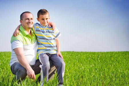 Father and son having a good time outdoor in wheat field photo