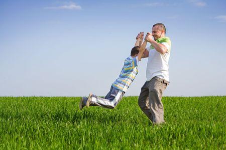 Padre e hijo pasar un buen rato al aire libre en el campo de trigo