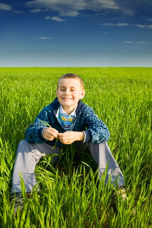 Cute kid in a wheat field, in a sunny day photo