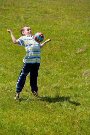 Cute boy playing football outdoor photo