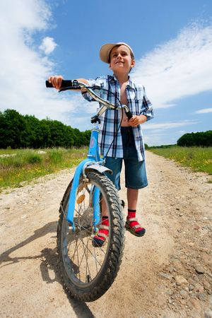 Beautiful boy with a bike on a country road photo