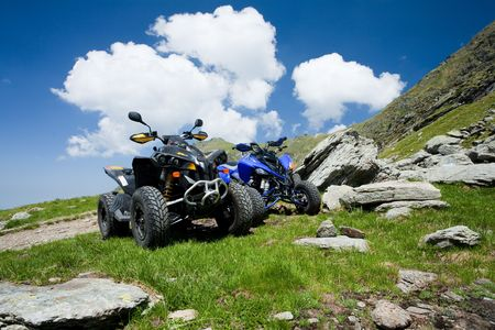 Image of all terrain vehicles on a mountain in a sunny day
