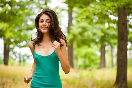 Beautiful young woman running or jogging through a forest, healthy life and sport concept