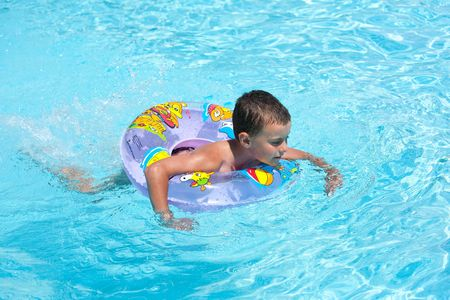 Cute kid swimming in a pool with clear water photo