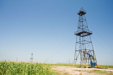 drilling well: Oil well field in a middle of a corn field. Agriculture and industry.