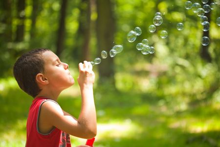 Cute kid blowing bubbles outdoors, in the forest in a beautiful sunny afternoon photo
