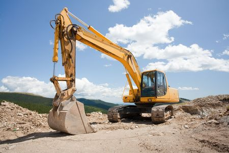 Excavator or digger (construction machinery) at a construction site outdoors