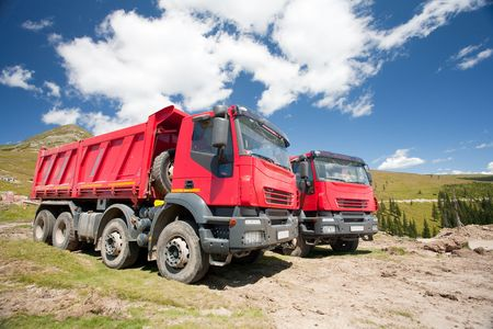 Two large red dump trucks at construction site, in a sunny summer day