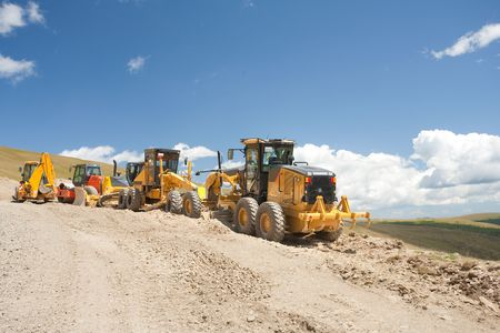 Excavators and construction machinery at a construction site outdoors photo