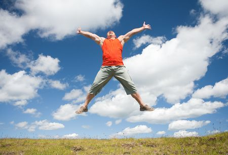 Young man jumping for joy in a beautiful landscape with blue sky and clouds Stock Photo