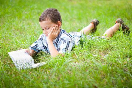 Cute kid reading a book while lying in grass photo