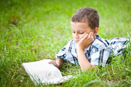 Cute kid reading a book while lying in grass