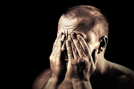Low key portrait of an young man covering his eyes photo