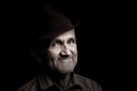 poor man: Portrait of an old man with hat, isolated on black