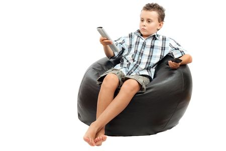Cute kid watching tv, sitting in a very comfortable and soft sack chair, with a remote control in his hand. photo