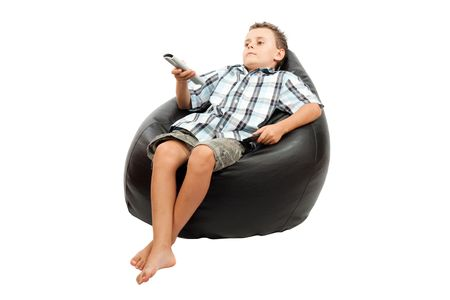 Cute kid watching tv, sitting in a very comfortable and soft sack chair, with a remote control in his hand.