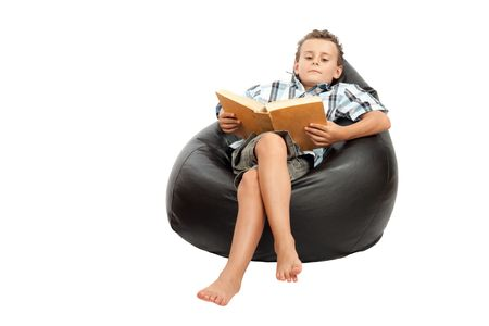 Adorable schoolboy reading a book while sitting in a comfortable sack chair, isolated on white Stock Photo - 5325045