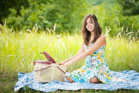 Beautiful young woman sitting on a blanket at picnic