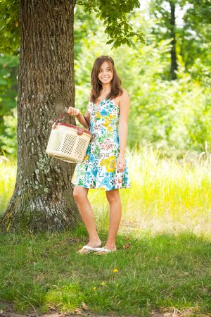 Beautiful young woman sitting on a blanket at picnic photo