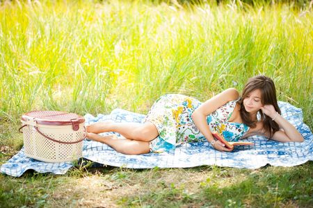 Beautiful young woman reading outdoor, lying on a blanket photo