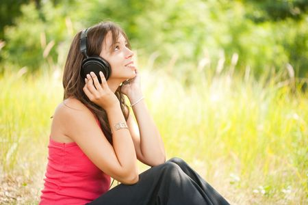 Portrait of a beautiful young woman listening music to headphones outdoor photo