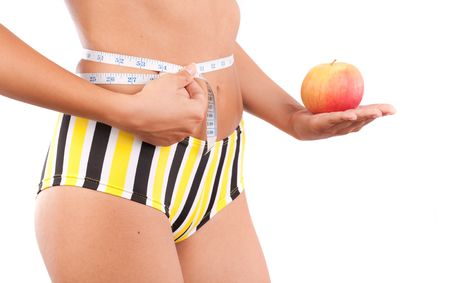 centimetres: Young slim woman holding an apple and a measurement tape around her torso Stock Photo