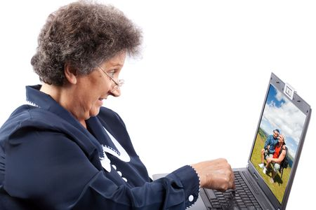 Old woman with glasses using computer photo
