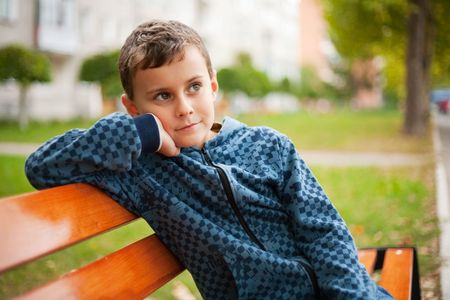 Cute kid sitting on a bench in a park photo