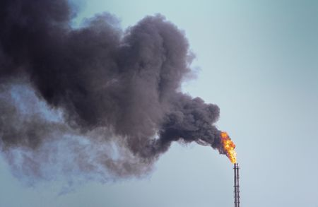 Refinery funnel burning with huge flame and throwing clouds of dark smoke
