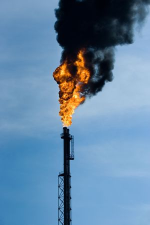 Refinery funnel burning with huge flame and throwing clouds of dark smoke photo