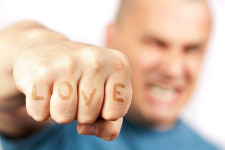 madman: Strong built aggressive man with word LOVE embossed into his knuckles punching towards the camera