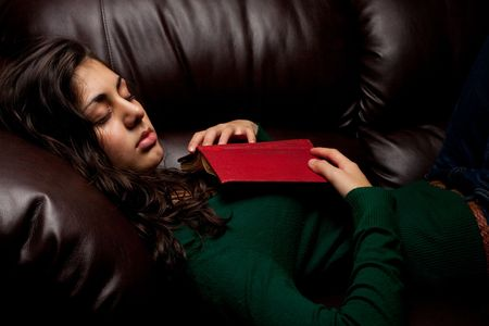 Beautiful young lady fallen asleep after reading a book, on a leather sofa photo