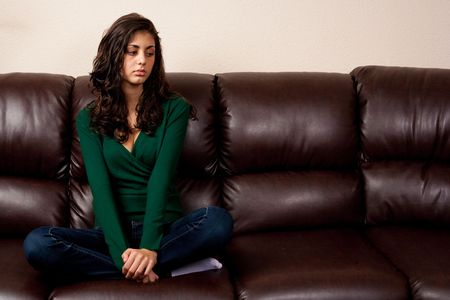 Portrait of a young lady sitting on a leather couch Stock Photo - 5726018