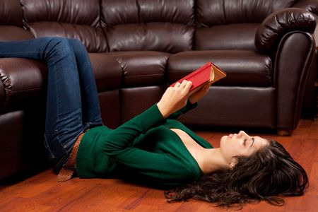 Beautiful young ethnic lady reading a vintage book on a leather sofa photo