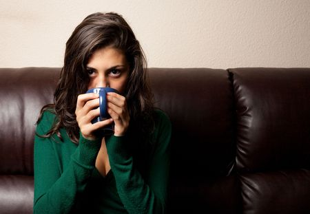 Beautiful brunette drinking tea or coffe while sitting on a leather couch photo