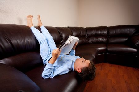 Cute schoolboy in pajamas reading a book (a dictionary) while sitting on a sofa upside down photo