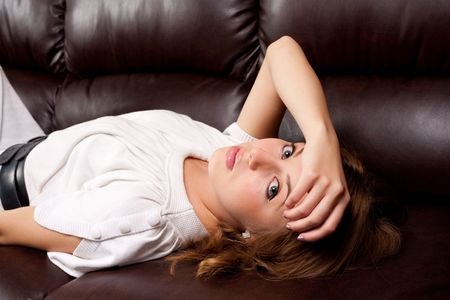 Portrait of a beautiful blonde on a leather couch photo