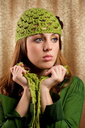 women subtle: Portrait of a beautiful blonde in retro cap and scarf over shiny curtain background