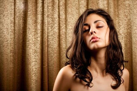 Glamour portrait of a beautiful brunette with a golden curtain in background