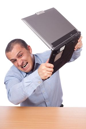 Angry businessman smashing his laptop on the table