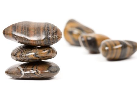 Close up of brown shiny zen stones, isolated on white background photo