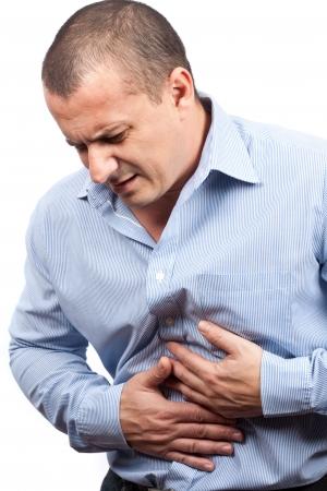 dolor de estomago: Joven con dolor de est�mago fuerte aislado sobre fondo blanco