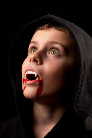 8 years old boy dressed as a vampire with fake blood and fangs