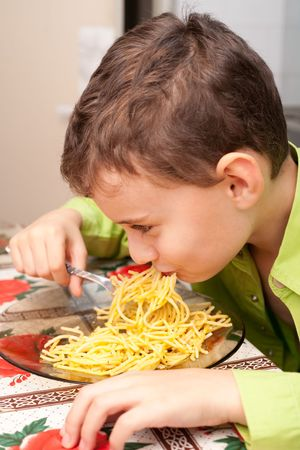 Cute kid eating delicious pasta, indoor shot Stock Photo - 6074881