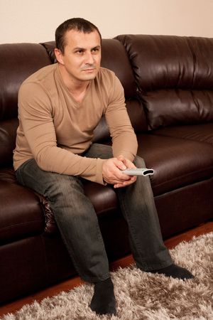 Portrait of a young man sitting on sofa watching tv photo