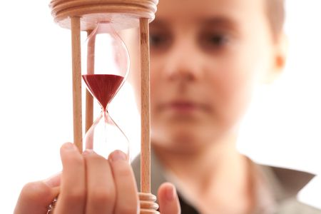 sand timer: Portrait of a schoolboy holding a hourglass, shallow depth of field Stock Photo