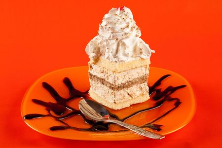 Close up of a delicious whipped cream (tiramisu) dessert isolated on orange background photo