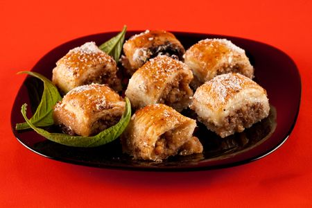Close up of traditional oriental cookies, baklava on black plate, isolated on orange background photo