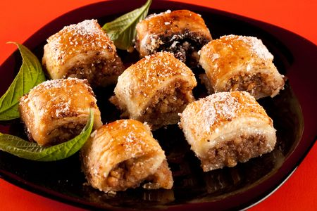 baklava: Close up of traditional oriental cookies, baklava on black plate, isolated on orange background