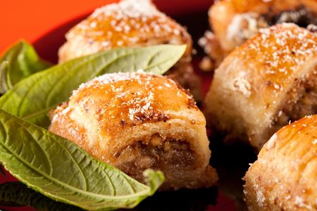 baklawa: Close up of traditional oriental cookies, baklava on black plate, isolated on orange background